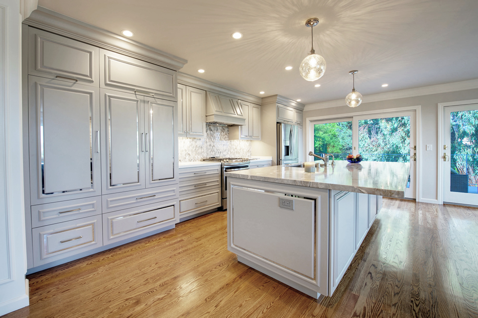 white island kitchen with chrome metal trim on cupboard doors