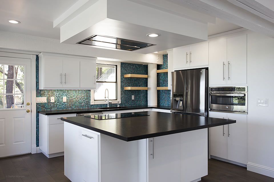 white kitchen with blue tile backsplash grey countertops and island