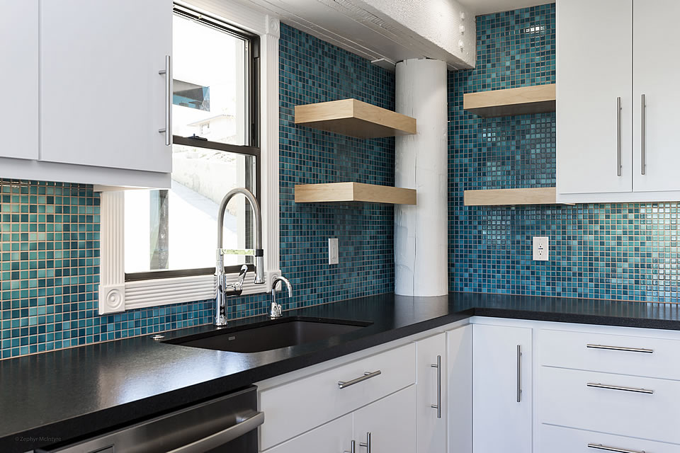 white cupboards charcoal counters blue tile backsplash